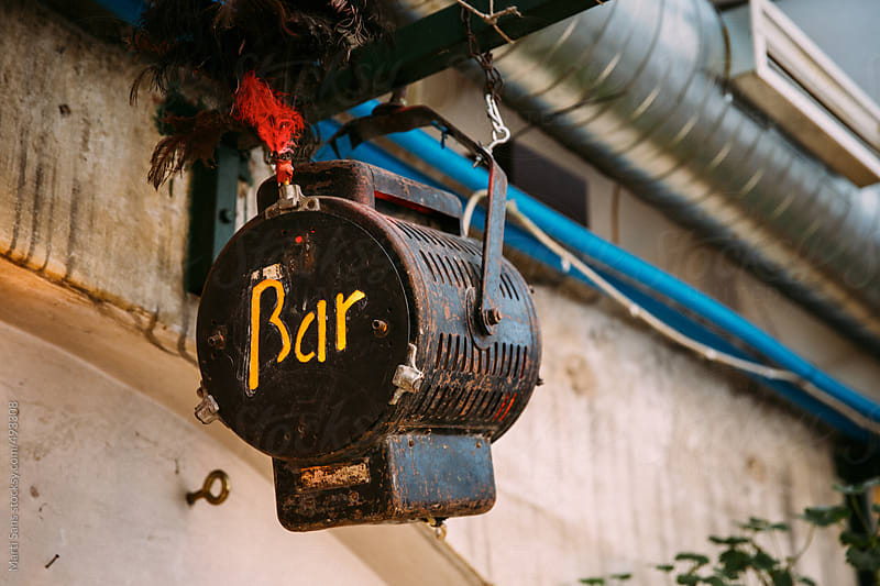 Bar word written on an outdoor lamp by Martí Sans for Stocksy United