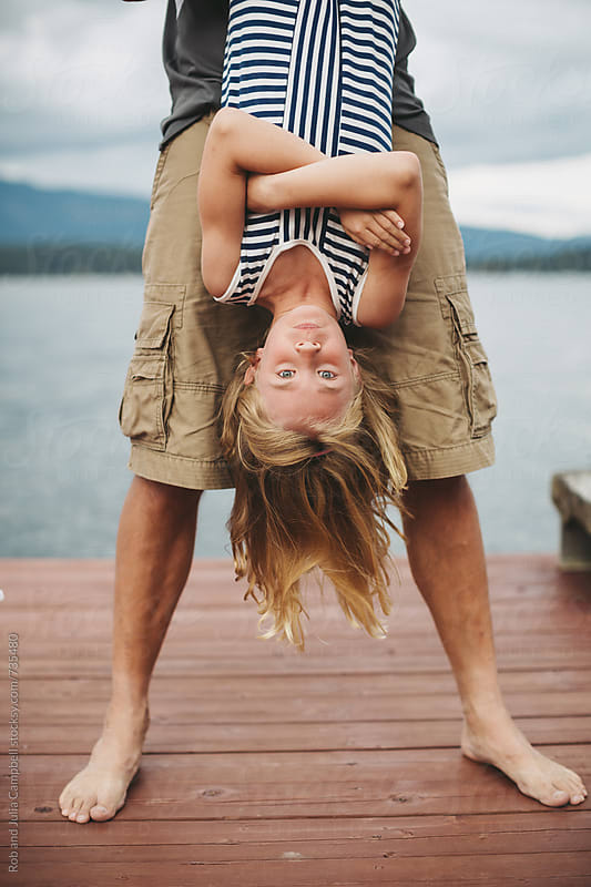 Young girl hanging upside down on the dock at the lake by Rob and Julia Campbell for Stocksy United