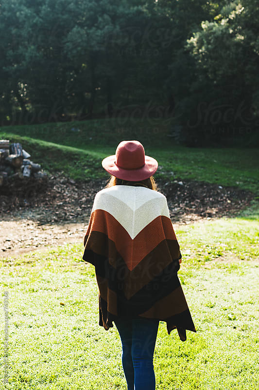 Back view of a woman walking in a rural landscape on winter. by BONNINSTUDIO for Stocksy United