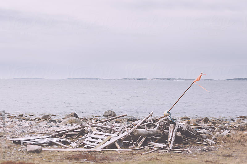 A pile of wreck wood on the beach by Jonas Räfling for Stocksy United