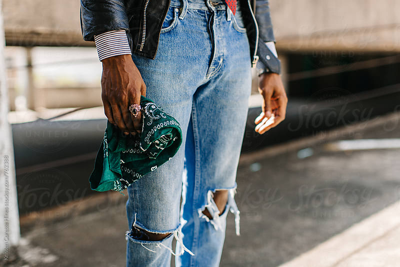 Up close shot of a man wearing a metal ring & ripped blue jeans by Kristen Curette Hines for Stocksy United