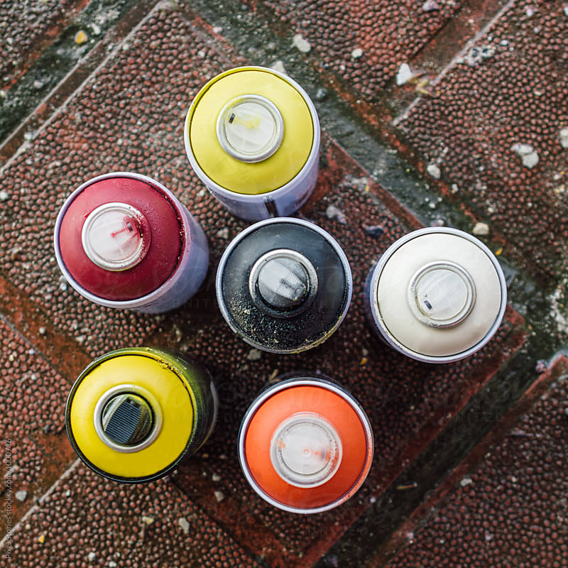 Colorful spray paint cans on the ground by Pixel Stories for Stocksy United