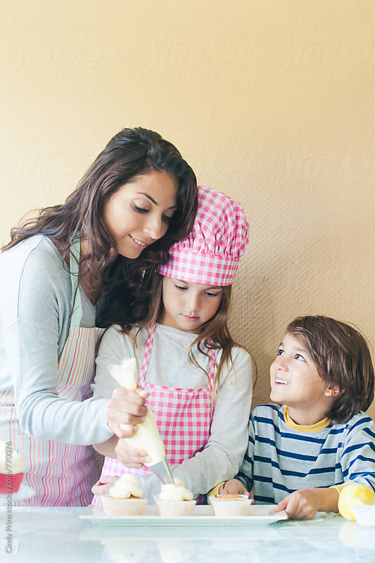Mother and her kids making cupcakes by Cindy Prins for Stocksy United