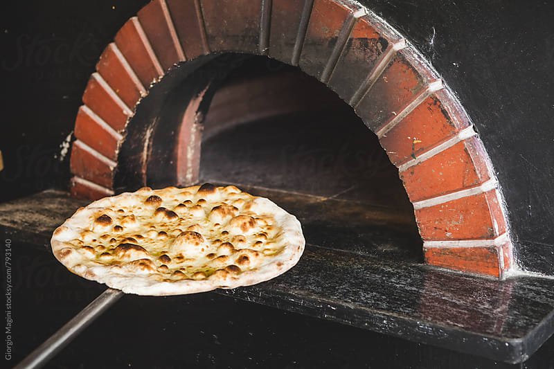 Baked Focaccia Pizza in front of a Wood Oven by Giorgio Magini for Stocksy United