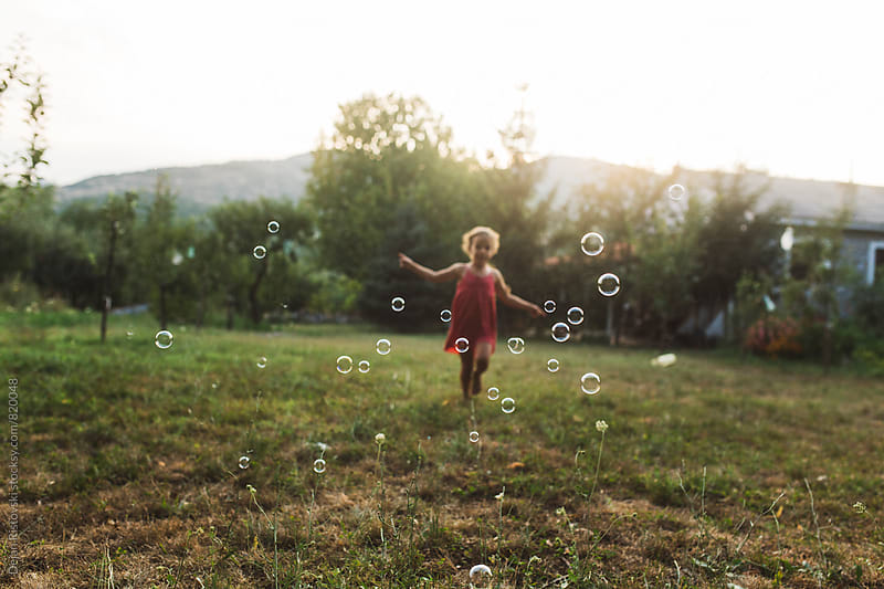 Playful child with bubble wand. by Dejan Ristovski for Stocksy United