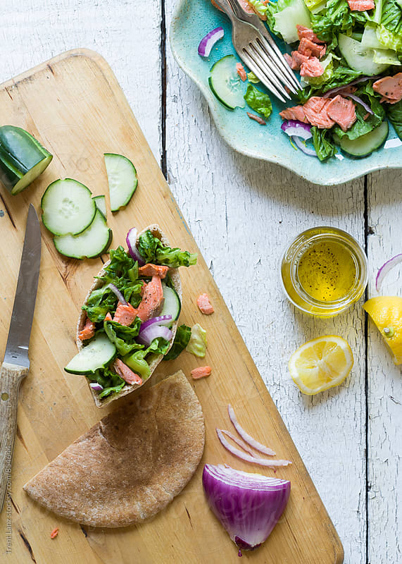 Salmon salad pita sandwich on wooden table by Trent Lanz for Stocksy United