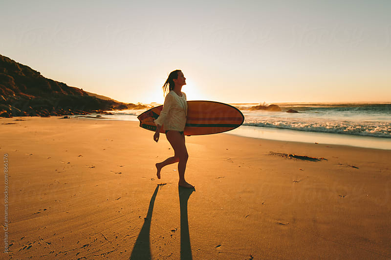 Young woman surfer with surfboard walking on beach at sunset by Jonathan Caramanus for Stocksy United
