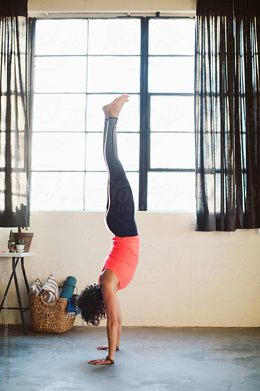 Young athletic woman doing handstand in her urban loft. by Kate Daigneault for Stocksy United