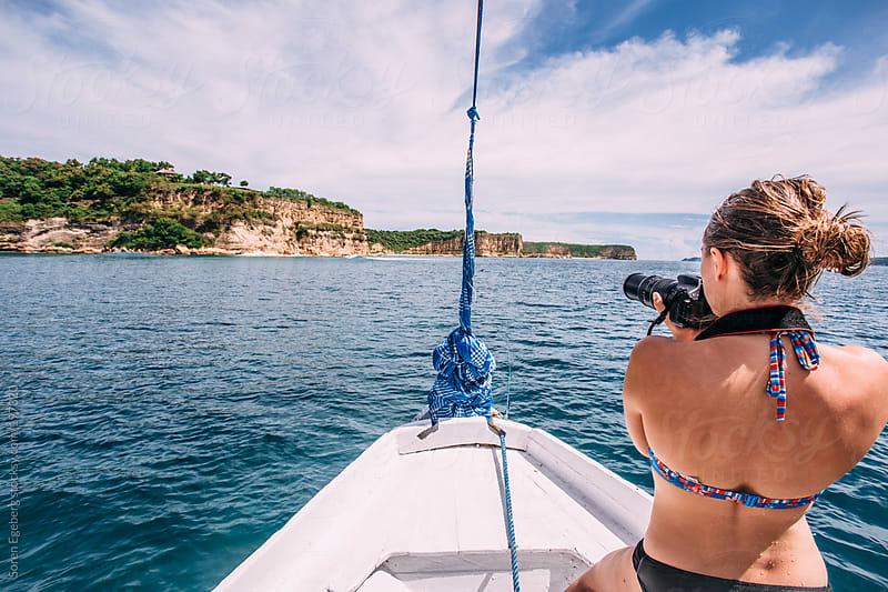 Blond girl in bikini on boat at sea taking photograph of ocean landscape by Soren Egeberg for Stocksy United