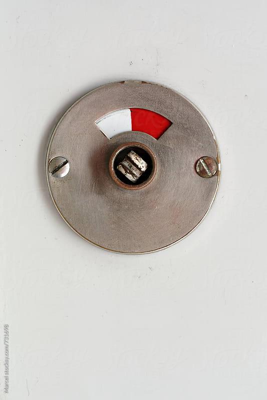 Bathroom lock indicator on a grey door by Marcel for Stocksy United