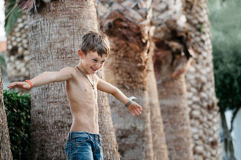 Boy imitating to be an airplane and ready to fly in front of palm trunks by Beatrix Boros for Stocksy United