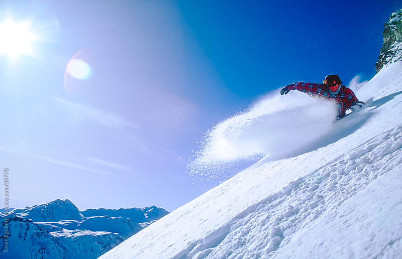 Snowboarder carving deep powder snow on sunny day in the mountains by Soren Egeberg for Stocksy United