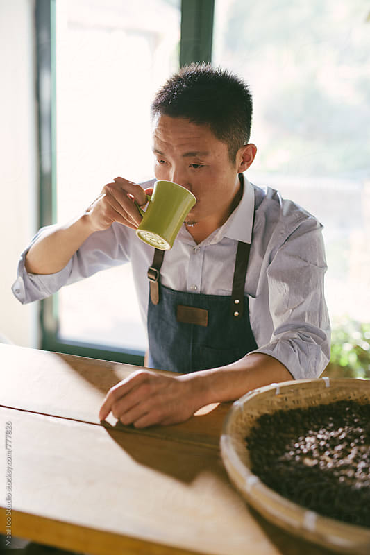 Portrait of young coffee maker drinking coffee by Maa Hoo for Stocksy United