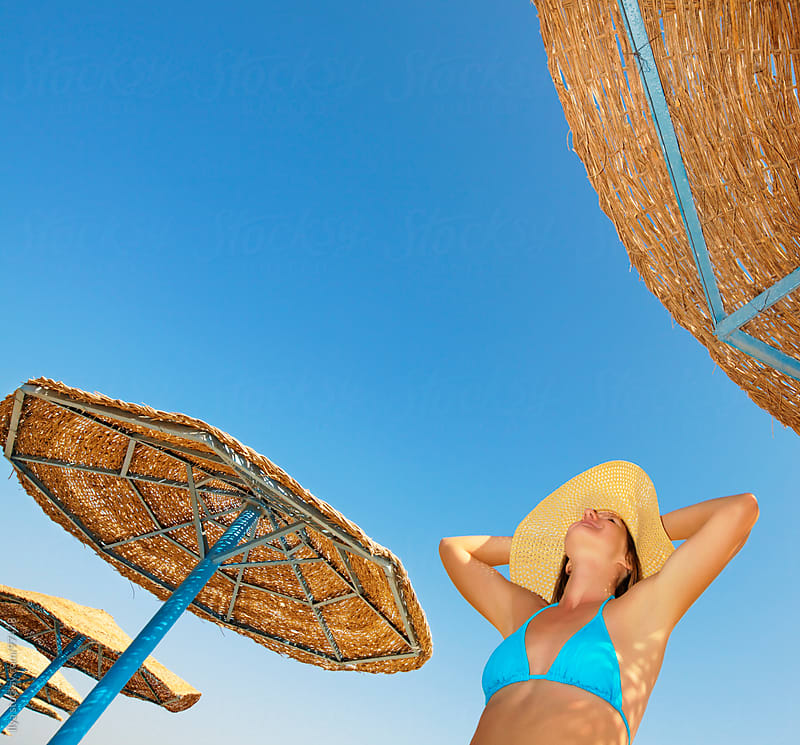 Young woman in bikini and sunhat under beach umbrellas. by Ilya for Stocksy United