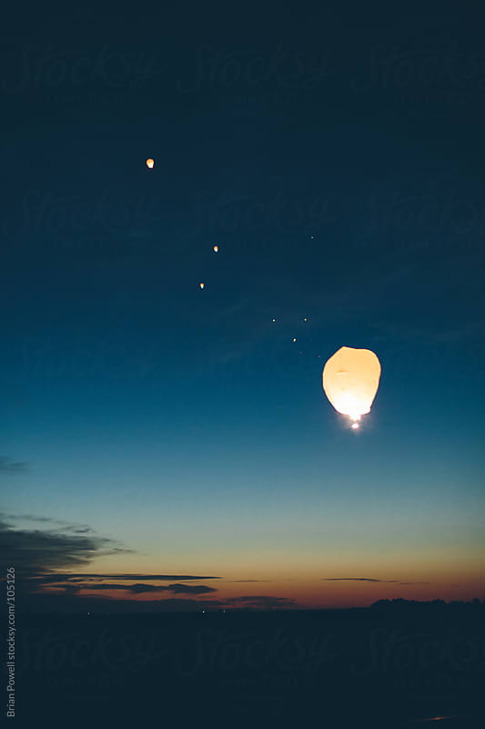 Chinese lanterns floating away at night by Brian Powell for Stocksy United