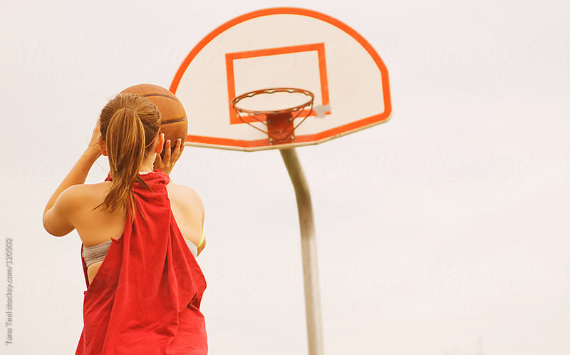 A teenage girl getting ready to shoot a basketball. by Tana Teel for Stocksy United