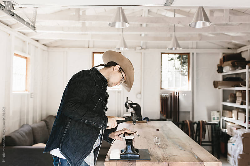 man making a leather belt in white studio by Nicole Mason for Stocksy United