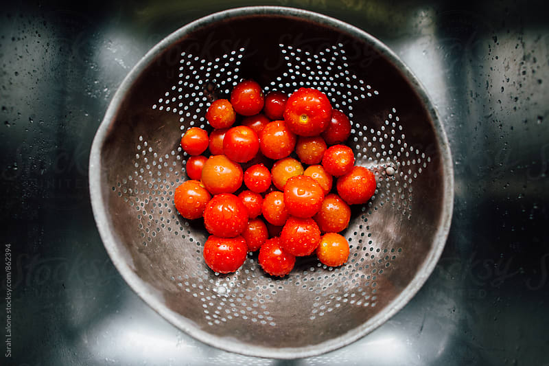 cherry tomatoes being washed in a colandar by Sarah Lalone for Stocksy United