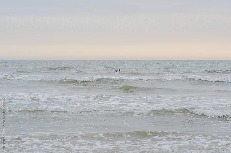 Female members of Family Swim in Atlantic Ocean Near Sunset by Brian McEntire for Stocksy United