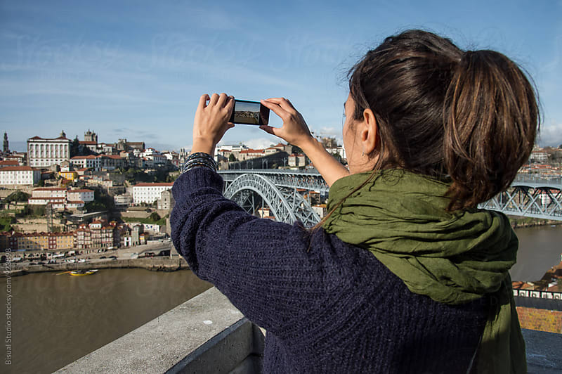 Young woman taking pictures of Oporto cityscape by Bisual Studio for Stocksy United