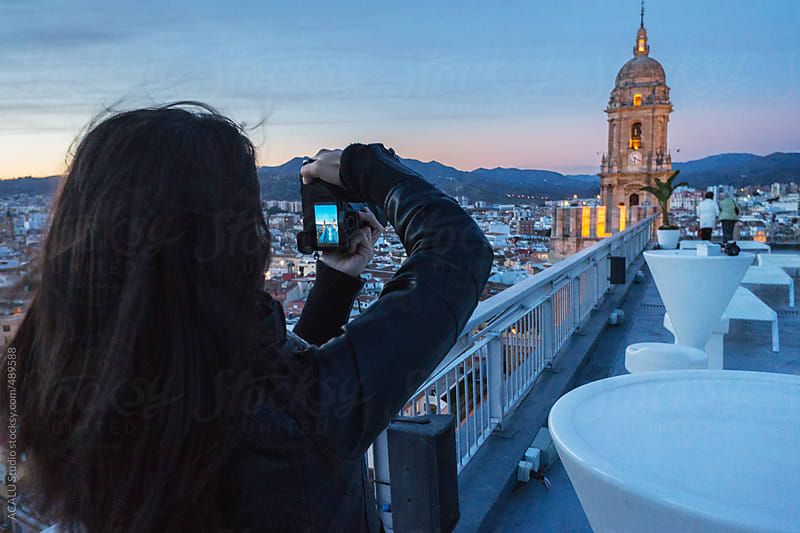 Young woman photographing Cathedral of Malaga by ACALU Studio for Stocksy United