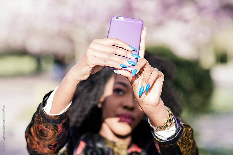 Closeup of a woman taking a picture on a mobile phone by Lior + Lone for Stocksy United