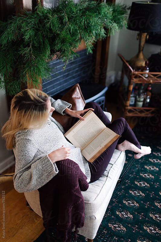 Woman reading a book over the Holidays by Kayla Snell for Stocksy United