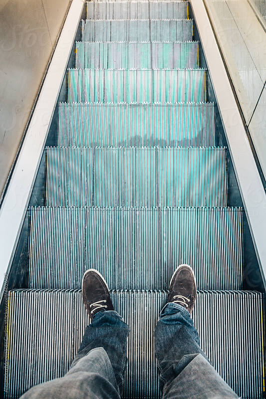 Feet of a man on escalator. POV vertical shot by Alejandro Moreno de Carlos for Stocksy United