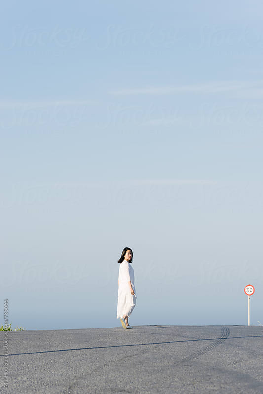 Chinese young girl walking on Santorini road by Maa Hoo for Stocksy United