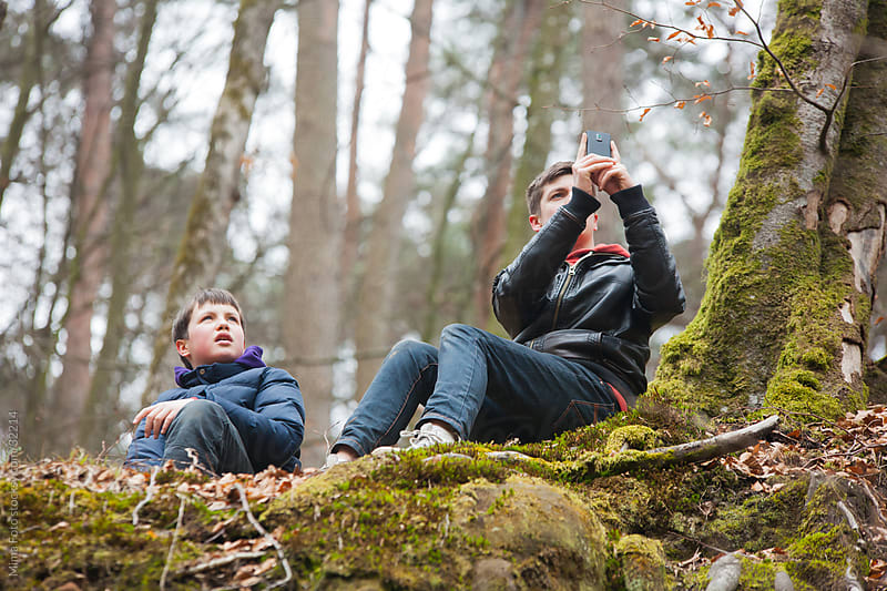 Teenage boys in the forest taking picture by Mima Foto for Stocksy United