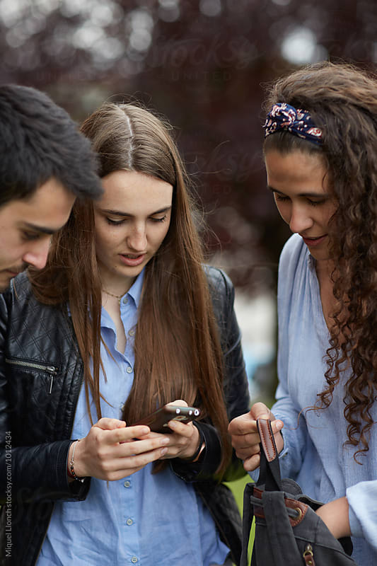 Young people sharing a phone chat outdoors by Miquel Llonch for Stocksy United