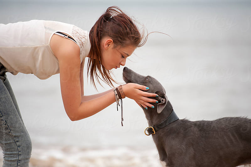 teenage girl kissing her pet dog by Lee Avison for Stocksy United