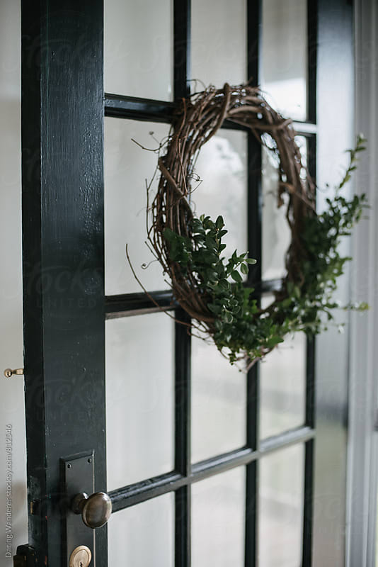 Simple diy boxwood wreath on vintage black door for the holidays by Daring Wanderer for Stocksy United