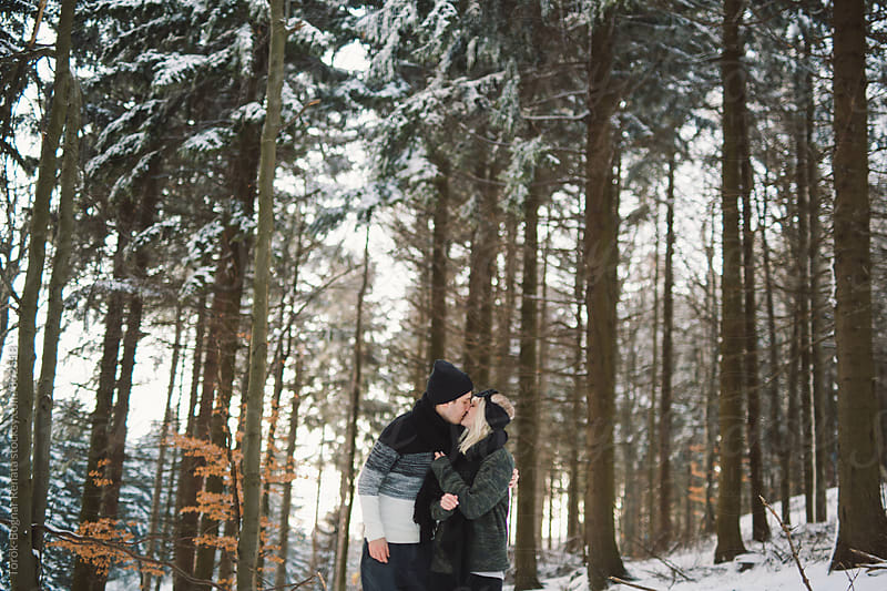 Lovely fashionable young couple in the snowy woods by Török-Bognár Renáta for Stocksy United