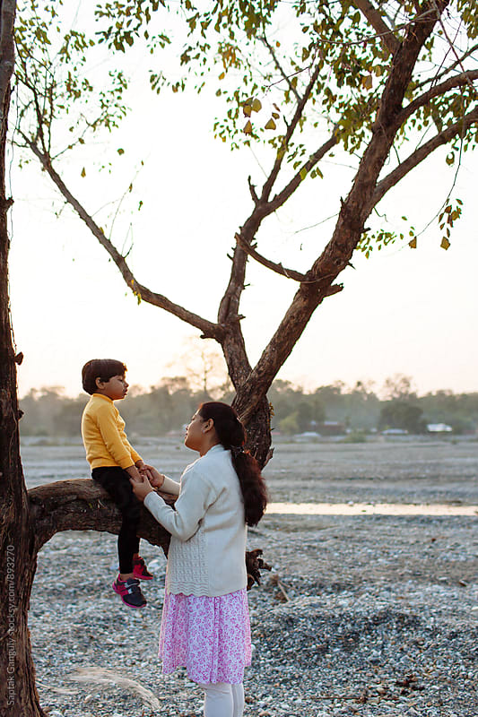Mother holding her daughter sitting on a tree branch by Saptak Ganguly for Stocksy United