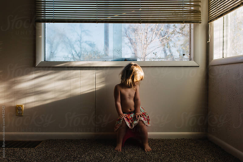 Toddler girl in skirt sitting in front of window by Jessica Byrum for Stocksy United