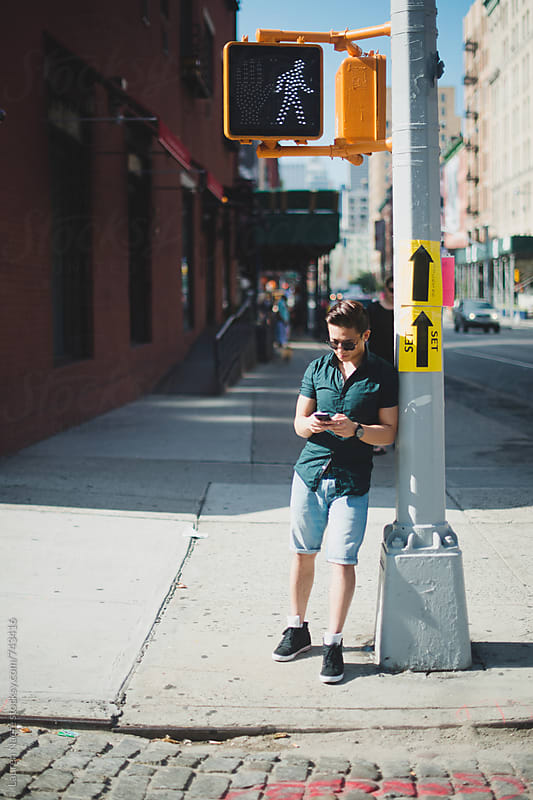 Man texting while standing in New York City street by Lauren Naefe for Stocksy United