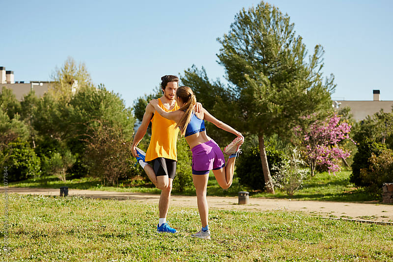 Athletes Stretching Legs In Park On Sunny Day by ALTO IMAGES for Stocksy United