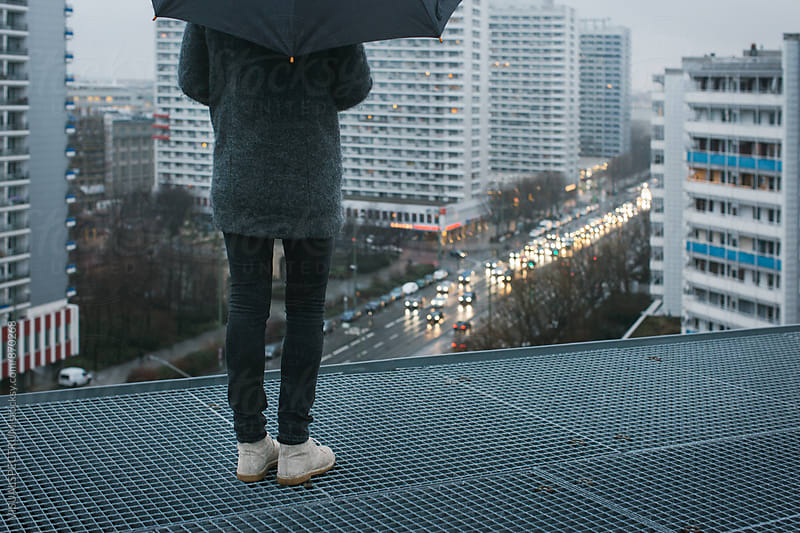 Woman With Umbrella Standing on Berlin Rooftop on Rainy Day by Julien L. Balmer for Stocksy United