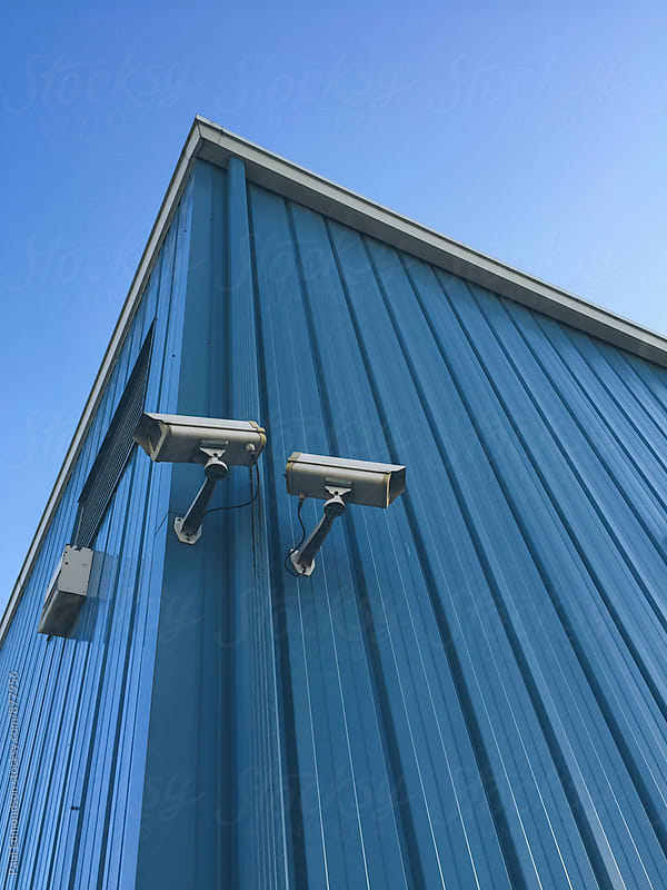 Surveillance cameras on building exterior by Paul Edmondson for Stocksy United