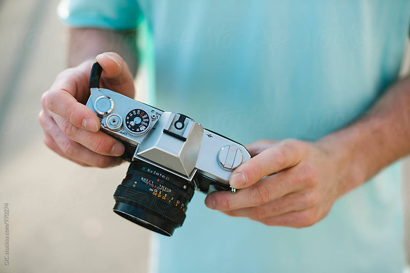 Photographer holding an analog camera by Simone Becchetti for Stocksy United
