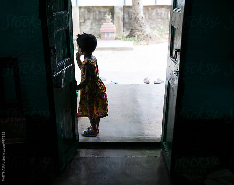 A little girl standing at the exit of a door by PARTHA PAL for Stocksy United