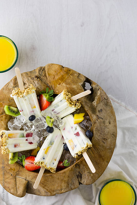 Wooden bowl of yogurt and fruit ice lollies by Kirsty Begg for Stocksy United
