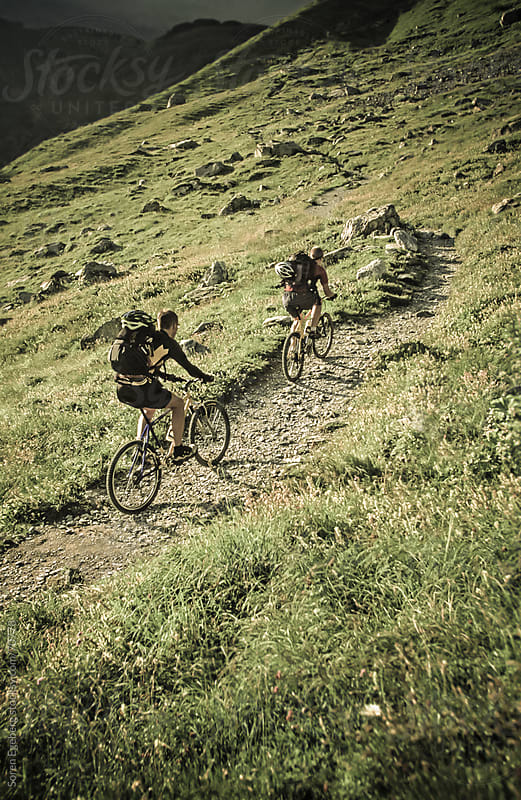 Two mountain bikers riding single track in the mountains  by Søren Egeberg Photography for Stocksy United