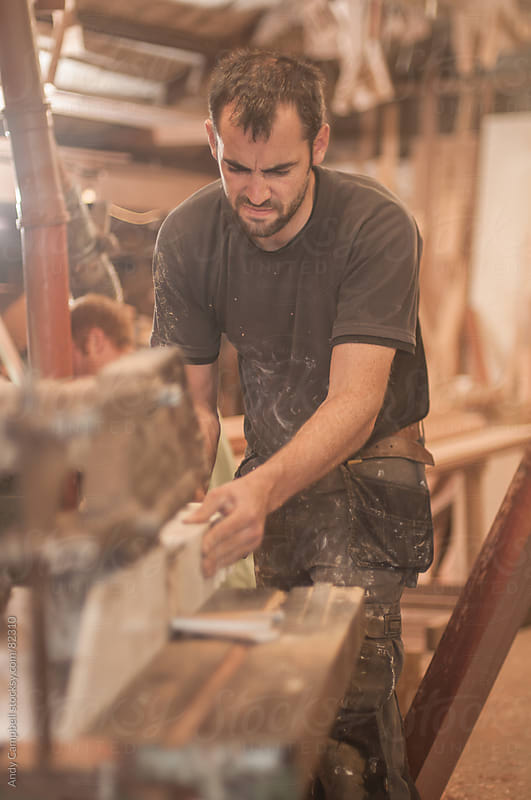 A carpenter using a power saw in a workshop by Andy Campbell for Stocksy United