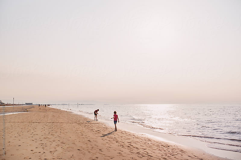 Children walking on a beach in the morning and looking for shells by Lea Csontos for Stocksy United
