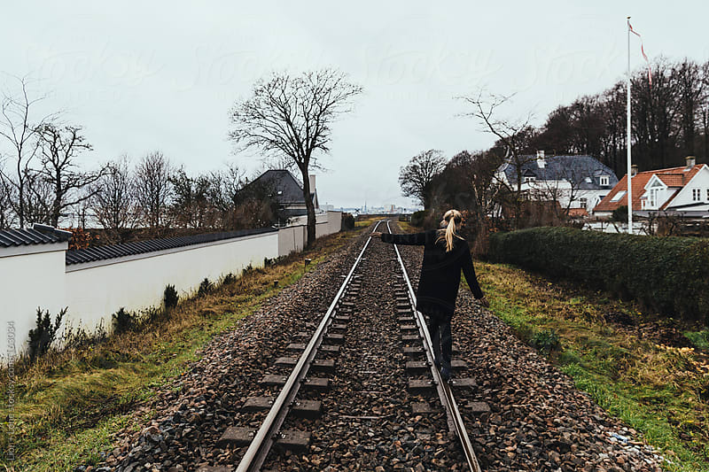 Blond woman walking on train tracks by Lior + Lone for Stocksy United