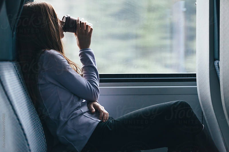 Young woman drinking coffee looking through train window by Ilya for Stocksy United