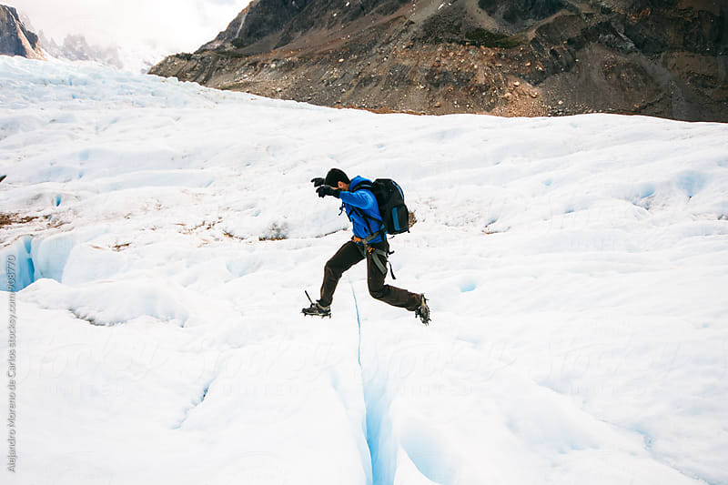 Side view of backpacker jumping on glacier by Alejandro Moreno de Carlos for Stocksy United