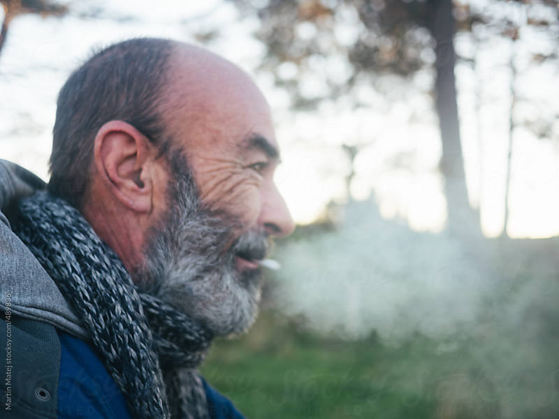 Old bearded man smoking a cigarette outside by Martin Matej for Stocksy United